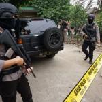 Petugas kepolisian bersenjata lengkap berjaga di rumah pelaku teror polisi saat dilakukan penggeledahan, di Sepatan, Kabupaten Tangerang, Banten, Kamis (20/10). Sejumlah barang bukti seperti senjata tajam, buku-buku, baut, pipa, solder dan sejumlah perangkat telepon diamankan pihak kepolisian guna penyelidikan lebih lanjut. ANTARA FOTO/Lucky R./ama/16