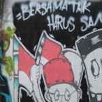 Warga melintas di dekat mural yang menyuarakan semangat kebersamaan dalam perbedaan di Jalan Kramat Jaya Baru, Jakarta Pusat, Senin (31/3/2014). Mural tersebut menjadi media bagi warga sekitar untuk menjaga kerukunan dan kedamaian di tengah perbedaan suku, agama, warna kulit, dan jender.