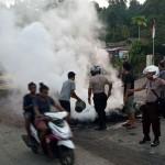 Petugas kepolisian bersama warga membersihkan ban yang dibakar seusai aksi di Jl.Essau Sesa Manokwari, Papua Barat. Foto: Media Indonesia/ANTARA/Toyiban